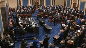 Crowd of old-white people raise their right hands as the Senate is sworn-in.